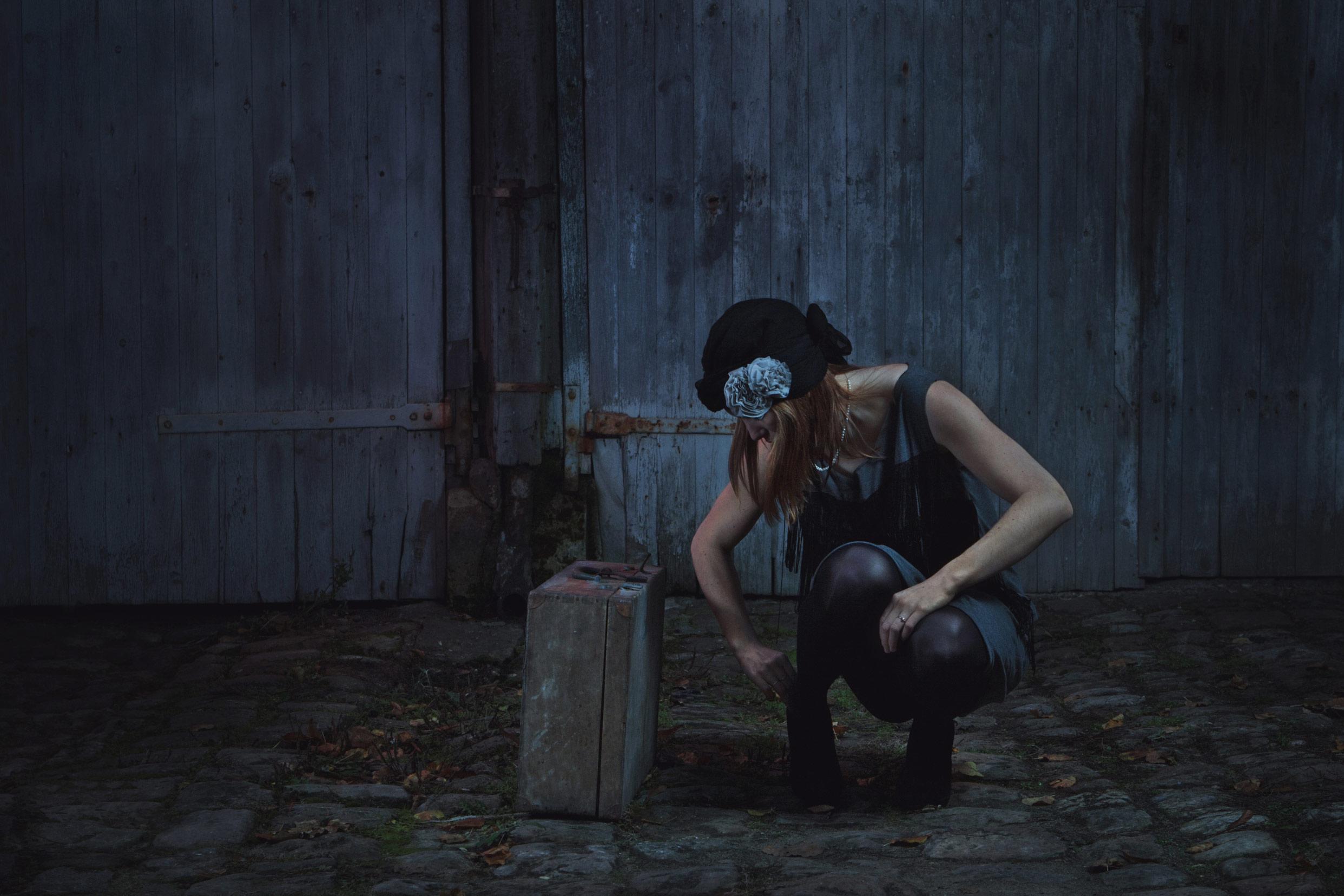 Image mettant en scène une femme accroupie dans une cour pavée de Pont Sainte Maxence