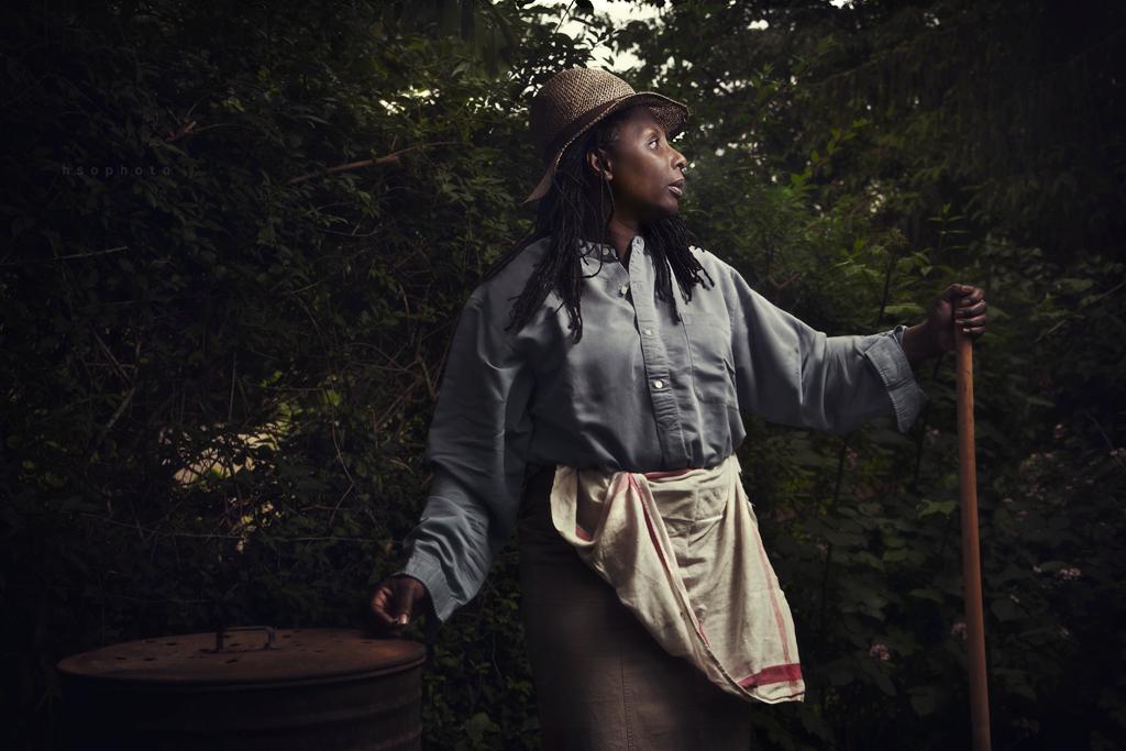 otographie mettant en scène une femme noire avec un chapeau dans un champ