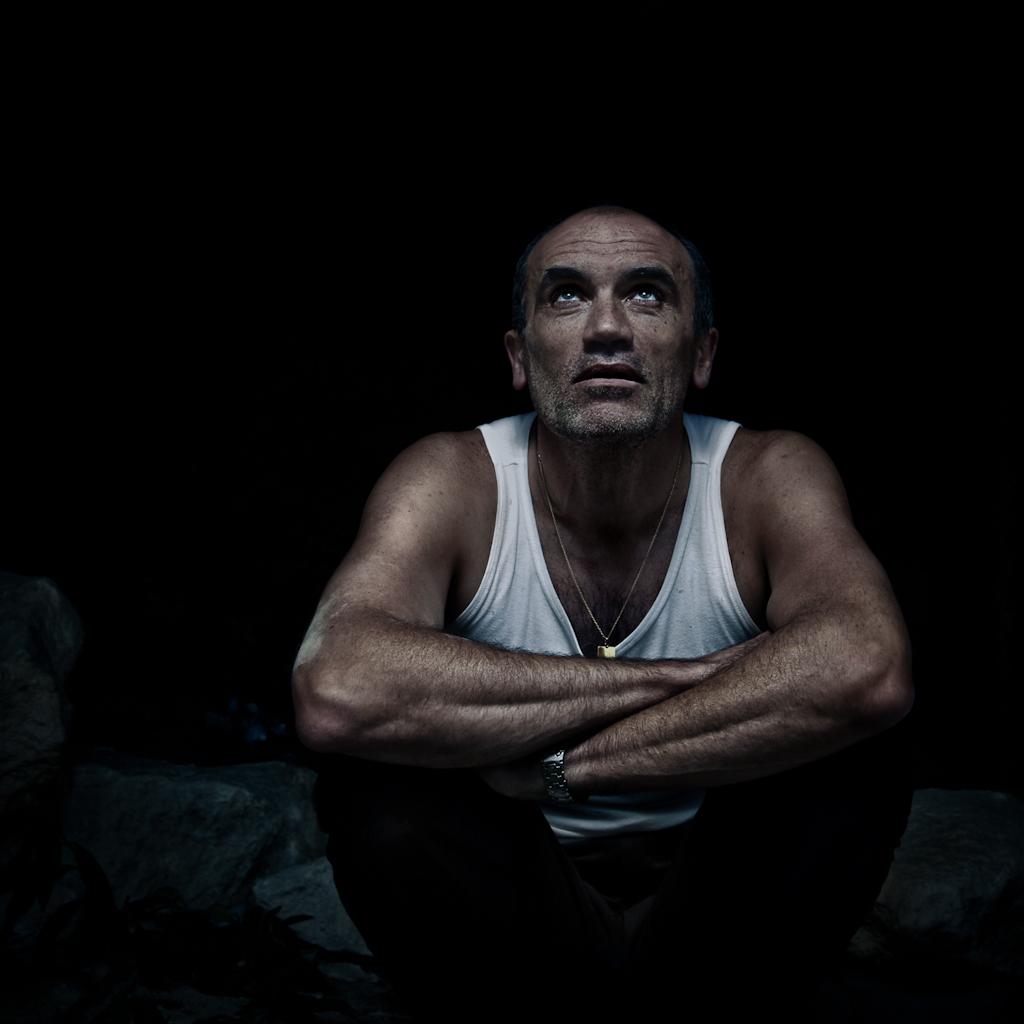 laurent courteau acteur pose en extérieur dans un endroit sombre
